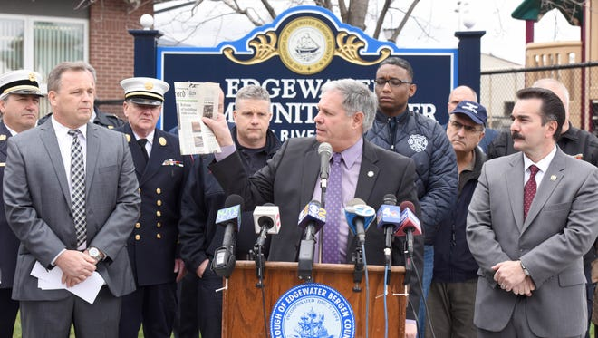 Bergen County Executive Jim Tedesco holds a copy of The Record newspaper with Edgewater Mayor Michael McPartland (left) and Assembly Speaker Vincent Prieto (D-Bergen/Hudson, right) while announcing new legislation to improve fire safety at multi-unit dwellings, both during construction and once buildings are occupied.