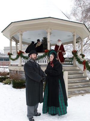 Dickens characters interact in front of the Skaneateles village gazebo with Father Christmas standing by.