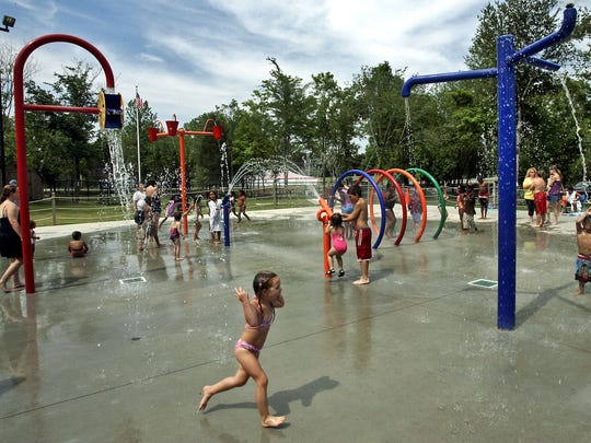 Kids play at the Splash Pad at Gregory Mill Park in