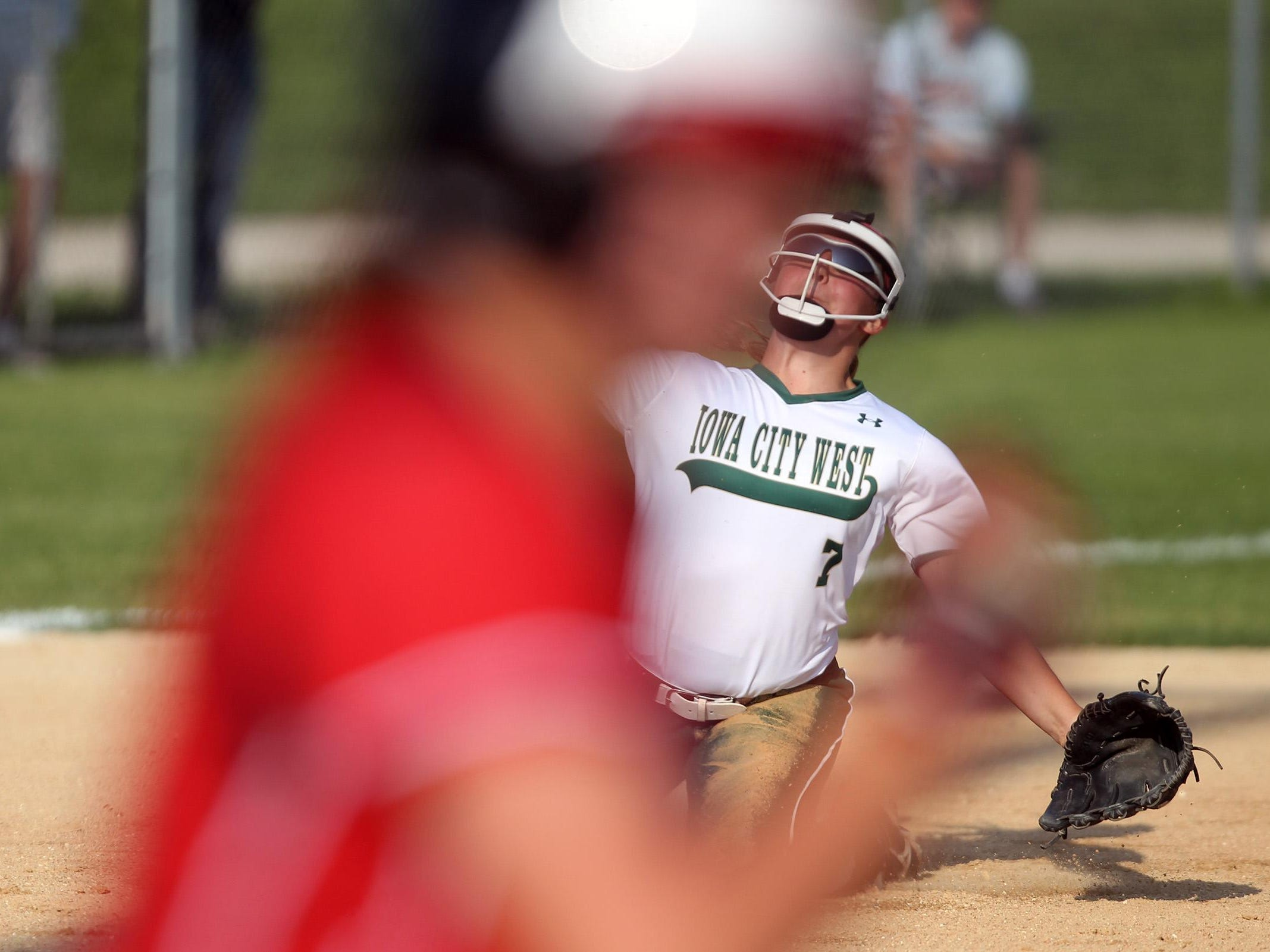 West High's Adara Opiola throws to first base during the Women of Troy's game against Linn-Mar on Thursday, July 9, 2015. David Scrivner / Iowa City Press-Citizen
