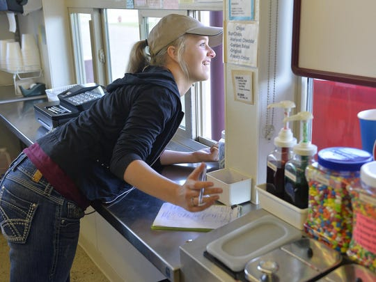 Mr. Twisty employee Anja Schumacher smiles as she takes an order from a customer Thursday at the St. Cloud restaurant.