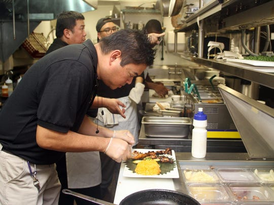 Chef Homer Reyes works in the kitchen at La Parilla de Manila, Wednesday, Aug. 19, 2015, in Colonia, NJ.