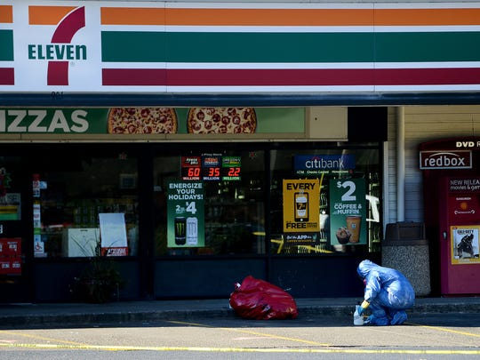 A worker cleans the curb outside the 7-Eleven where Linfield College sophomore Parker Moore was fatally stabbed Saturday night. Photographed in McMinnville, Ore., on Sunday, Nov. 16, 2014.