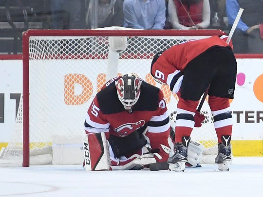 New Jersey Devils left wing Taylor Hall (9) checks on New Jersey Devils goaltender Cory Schneider (35) after a hard hit in the third period. The Devils defeat the Lightning 5-2 in Game 3 of Round 1 of the Stanley Cup Playoffs at the Prudential Center in Newark, NJ on Monday, April 16, 2018. The series is 2-1, Tampa Bay.