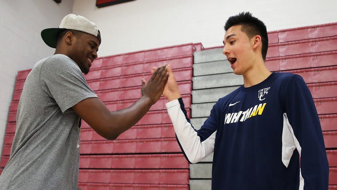 Whitman College basketball players have come up with their own individual handshakes before a came, with the help of their coach.  From left to right demonstrating are Montez White and Jeff Kenney.