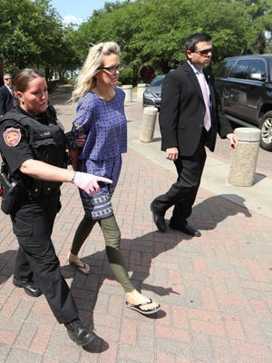 Denise Merrell Williams, 48, is led out of her accounting office at Doak Campbell Stadium in handcuffs Tuesday, after a Leon County grand jury indicted her on a charge of first-degree murder of Mike Williams.