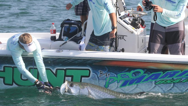 Members of team Sea Hunt/Pro Marine record the size and weight of their catch during the Professional Tarpon Tournament Series in Boca Grande Pass. Their tarpon weighed in at 139 pounds.