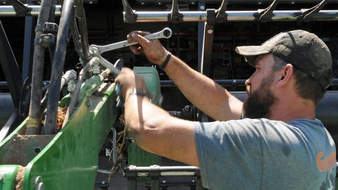 "Kevin Kejr tightens a new hydraulic hose on a 45-foot combine header in preparation of this year's harvest at the Kejr Farm outside Brookville on Thursday. ""Harvest is always a fun time to spend with family on the family farm. I came back this year to help out,"" said Kejr."