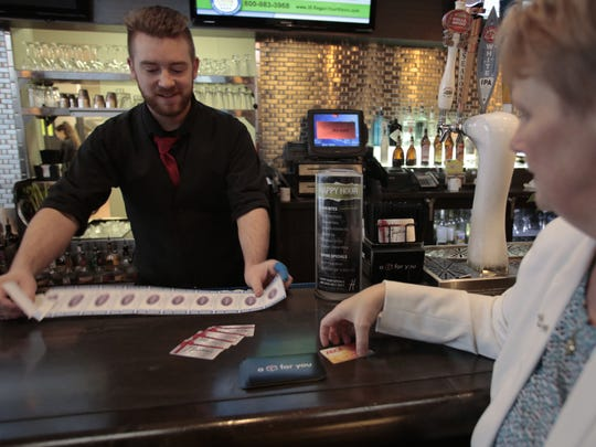 Zachary Allen of Westland spreads out movie passes as Kris Hruska of Canton readies her credit card to purchase them on Thursday at Hayden's restaurant in Canton.