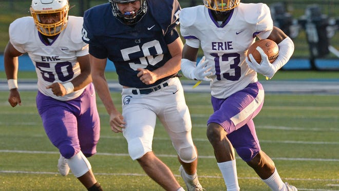 Erie High School senior Naseer Pacely, right, picks up a first down against McDowell at Gus Anderson Field on Sept. 11, 2020, in Millcreek Township. This was the first game of the season, viewed by a limited number of fans due to the COVID-19 coronavirus pandemic. [GREG WOHLFORD/ERIE TIMES-NEWS]