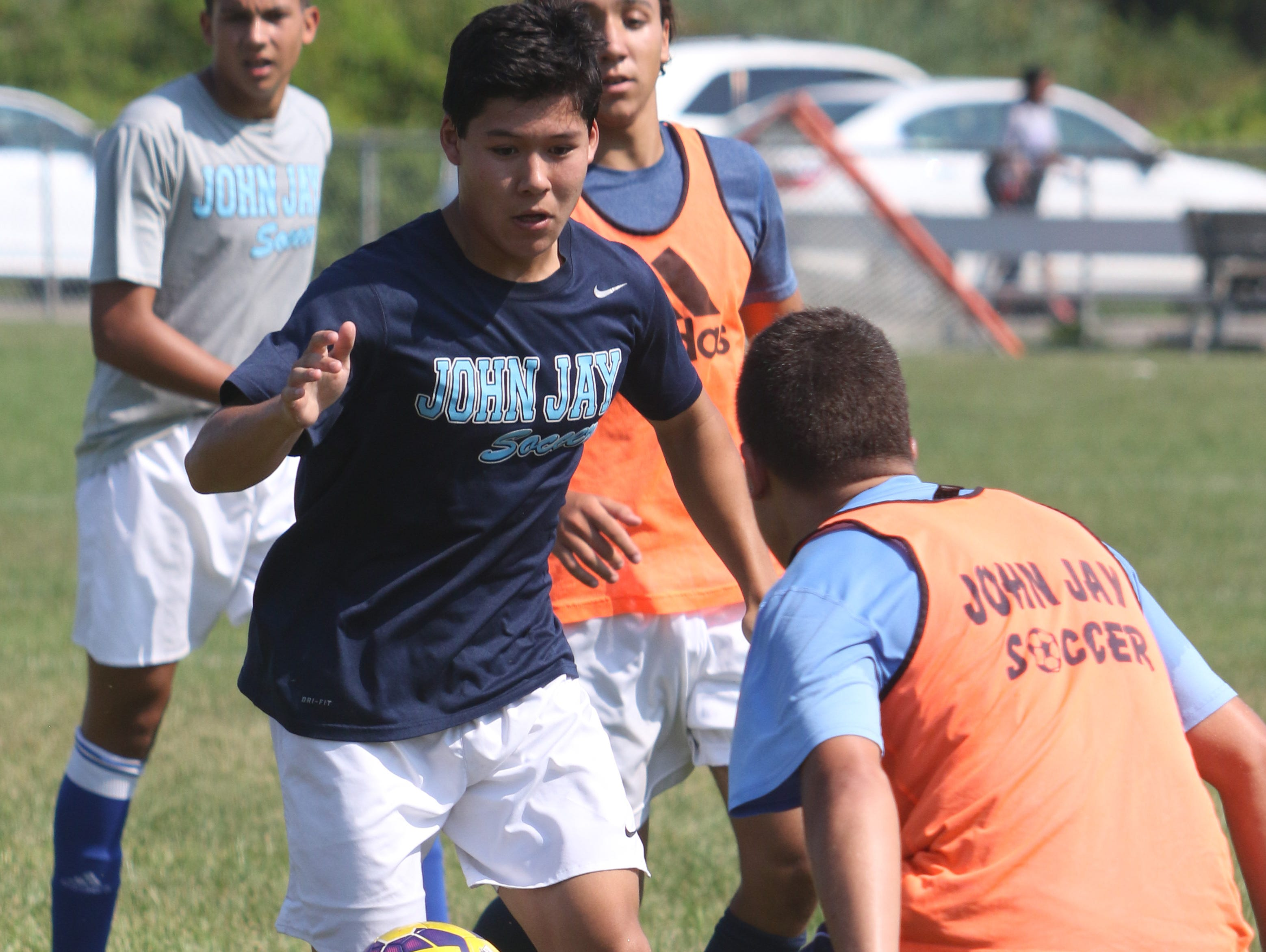 John Jay High School's Nick Dillmann dribbles around a teammate during practice on Wednesday.