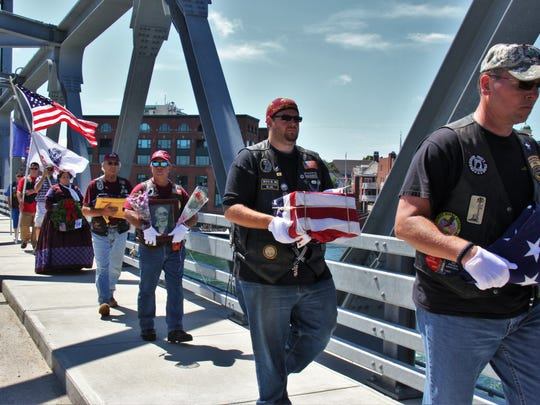 Patriot Guard Riders dismount near the New Hampshire border and carry the flag-draped box containing the ashes of Civil War veteran Jewett Williams across the Piscataqua River on the Memorial Bridge and into Maine.