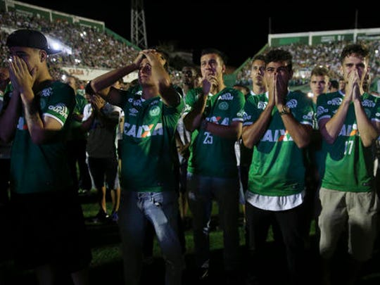 Chapecoense soccer players who did not travel with their team on a flight to Colombia that crashed, mourn during a tribute with fans to their late teammates at Arena Condado stadium in Chapeco, Brazil, Wednesday, Nov. 30, 2016. Authorities were working to finish identifying the bodies before repatriating them to Brazil.