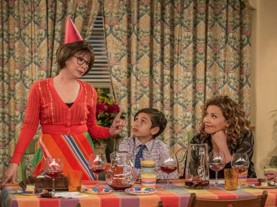 """This image released by Netflix shows Rita Moreno, from left, Marcel Ruiz and Justina Machado in a scene from """"One Day At A Time."""" The series, a remake of the 1970's-80's Norman Lear TV series, centers on a Cuban-American family. It debuts on Netflix on Sunday."""