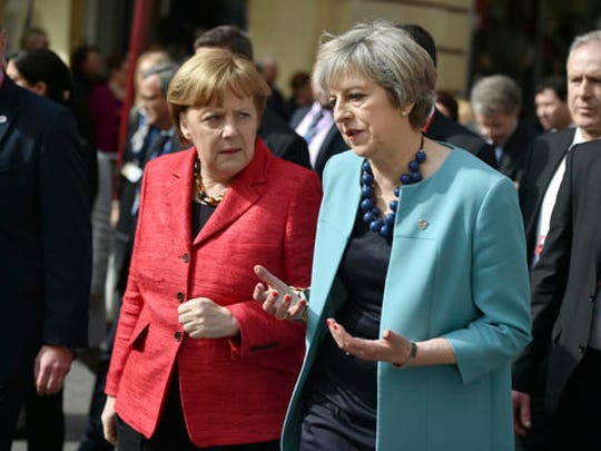 British Prime Minister Theresa May, center right, speaks with German Chancellor Angela Merkel, center left, as they walk during an event at an EU summit in Valletta, Malta, on Friday, Feb. 3, 2017. European Union heads of state and government gathered Friday for a one day summit to discuss migration and the future of the EU.