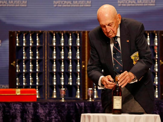 """FILE – In this Nov. 9, 2013, file photo, retired U.S. Air Force Lt. Col. Richard """"Dick"""" Cole, a surviving member of the 1942 raid on Tokyo led by Lt. Col. Jimmy Doolittle, opens an 1896 bottle of cognac the Raiders had been saving for their final toast, at the National Museum of the U.S. Air Force at Wright-Patterson Air Force Base in Dayton, Ohio. Cole, co-pilot of the Doolittle Tokyo Raiders' lead plane and a fly-over by vintage B-25 bombers will be part of Ohio events April 17-18, 2017 for the 75th anniversary of the daring attack that helped turn the tide of World War II. (AP Photo/Al Behrman, File)"""