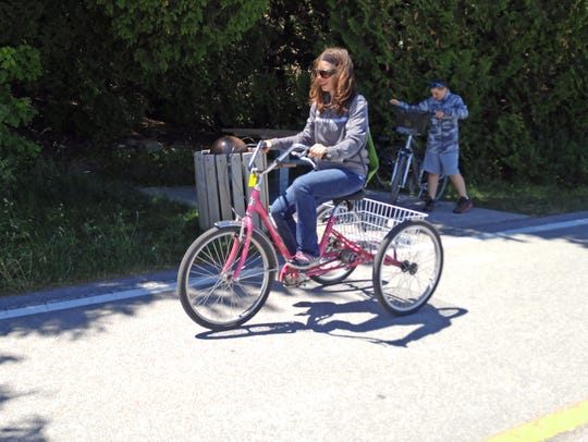 Alexis Myers rides a tricycle on Mackinac Island in
