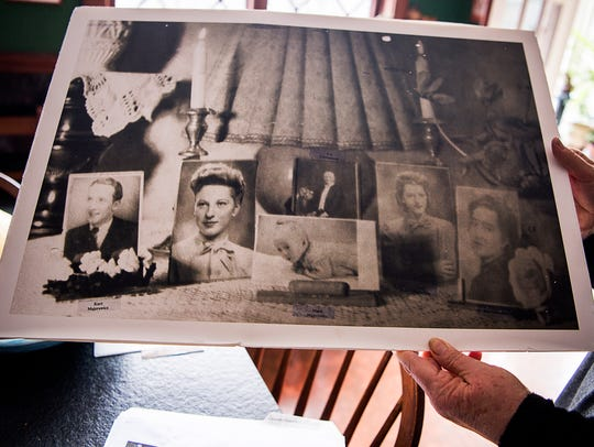 Sharon Faher holds up a collage of family photographs.