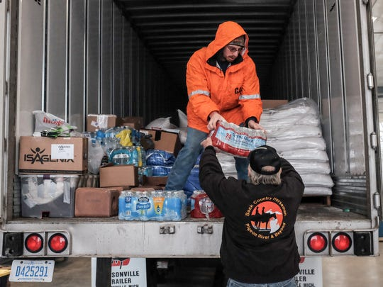 Dick Kleinhardt hands Mike Long, on the truck, supplies for farmers in some western states hurt by the recent wildfires. A convoy of over 40 trucks will make the trip.