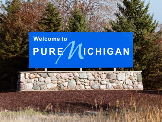 Blue welcome to pure michigan sign on a stone wall