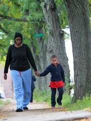 Tiffany Greenfiled, 29,  sister of Tanasia Milligan, walks Milligan's 5-year-old son, Ethan, home from school last month to her house, where she is helping care for him.