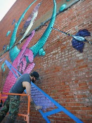 Artist Daniel Gulick works Thursday morning on a mural