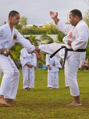 From left, Edmund Borja and instructor Errol Lee practice blocking kicks during a karate training session at Matapang Beach Park in Tumon on April 11.