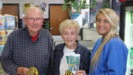 Mardell Stangel, middle, and her husband, Paul, recently won private suite tickets to the Nov. 15 Detroit Lions at Green Bay Packers game, which were presented to them by Bryanna Fuller, right.