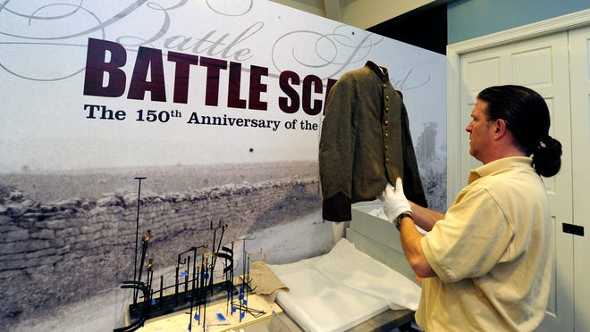 "Doug Zellman of 1220 Exhibits Inc. prepares a Civil War artifact of a soldier's coat to be displayed at the Battle of Franklin Trust's ""Battle Scarred"" Civil War exhibit, which opens to the public Saturday at Carnton Plantation. This exhibit will be a rare and sometimes first-ever glimpse at artifacts, papers and photos from the Battle of Franklin."