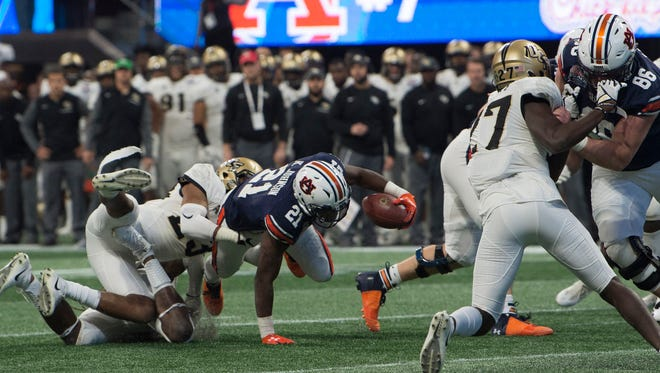 Auburn running back Kerryon Johnson (21) dives forward as UCF defensive back Tre Neal (23) tackles him during the second half of the Peach Bowl between Auburn and UCF on Monday, Jan. 1, 2018, at Mercedes-Benz Stadium in Atlanta, Ga.