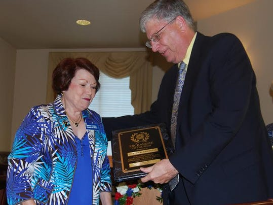 Club President Ed Temple, right, is shown presenting the Exchangite of the Year plaque to Martha Channell.