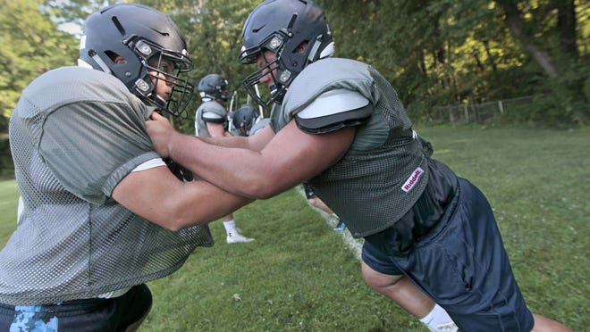 Thomas's Jeff Aspenleiter, OL/DL, left, and Nick Zona, C/NG, lock up during line blocking drills at practice at Webster Thomas High School Wednesday.