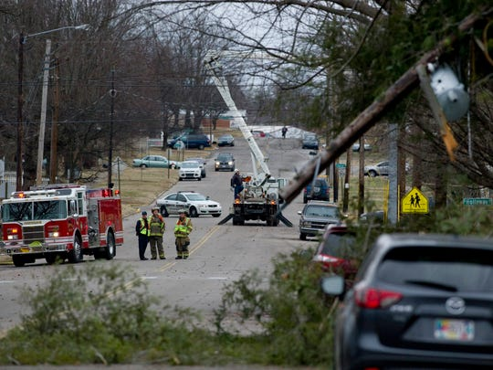 Emergency personnel, including firemen and utility workers, respond to a downed tree across a power line at 810 Center Street in Henderson, Ky., Tuesday afternoon. The tall pine tree in Conner Mattingly's front yard was toppled by heavy wind out of the south. Luckily for Mattingly, a math teacher at Henderson County High School, the tree fell away from his home and caused no damage to his house. Power was knocked out in the neighborhood, but nobody was hurt.