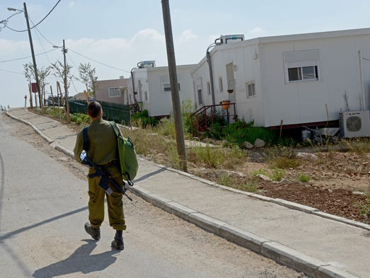 An Israeli soldier walks past houses in the Gva'ot Settlement in the Gush Etzion bloc in the West Bank, Sept. 3.