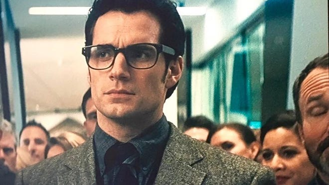 "Nakyshia Galloway stands behind Clark Kent (Henry Cavill) in ""Batman v Superman.""She is in a gold cocktail dress, tanned face, and dark hair behind Henry Cavill's shoulder."