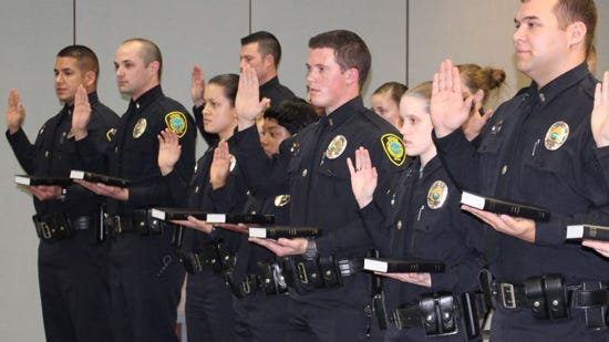 A new group of cadets are sworn in as Asheville police officers in January. Despite attempts to increase the number of black officers, the percentage of African Americans in the force has dropped since 1998.