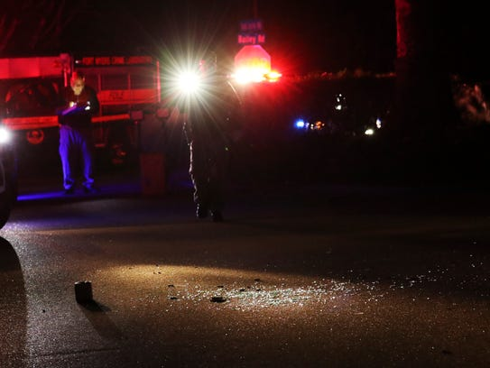 Law enforcement officials work the scene of an officer