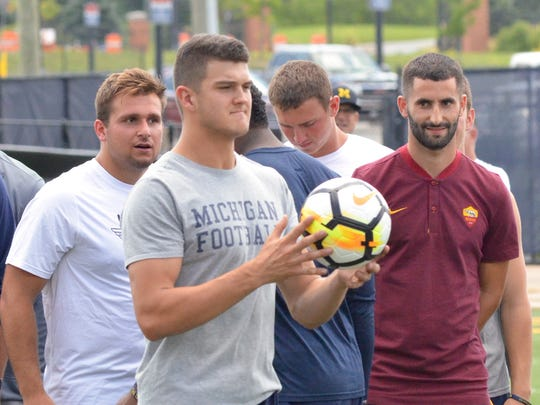 Michigan quarterback John O'Korn holds a soccer ball as the U-M football team and AS Roma work out on Monday, July 17, 2017, in Ann Arbor.