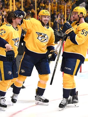 Predators right wing Craig Smith (15) pats left wing Kevin Fiala (22) on the head as defenseman Roman Josi (59) looks on after Fiala scored the game-winning goal during the second overtime in Game 2 of the second round NHL Stanley Cup Playoffs at  Bridgestone Arena Sunday, April 29, 2018, in Nashville, Tenn.