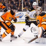The Philadelphia Flyers' Andrew MacDonald (47) moves to clear the puck away from Boston Bruins' David Pastrnak (88), on the rebound from a shot on the Flyers' Steve Mason (35) during the second period of Saturday's game in Boston.