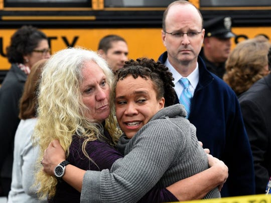Clovis Stair, left, supervisor of Knox County School psychology, consoles Sunnyview Primary School Principal Sydney Upton near the scene where two school buses serving Chilhowee Intermediate School and Sunnyview Primary School crashed on Asheville Hwy just east of Gov. John Sevier Highway Tuesday, Dec. 2, 2014