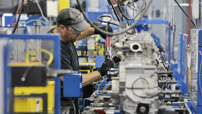 A worker assembles four-stroke all-terrain vehicle engines July 31, 2015, at the St. Cloud Arctic Cat engine assembly facility.