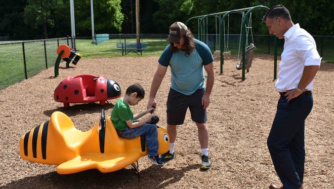 Miles Fenichel plays on the Bumble Bee Spring Rider as County Executive Mike Hein and parents Justin Fenichel and Catalina Moreno look on.
