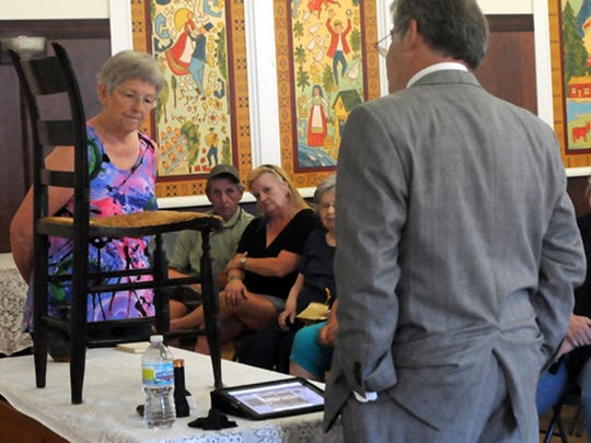 "Antiques appraiser Mark Moran looks over a Hitchcock chair owned by Gretchen Maring of Ellison Bay, left, during the Ephraim Historical Foundation-sponsored the ""What's it Worth?"" show hosted by Moran at Ephraim Village Hall in 2012."
