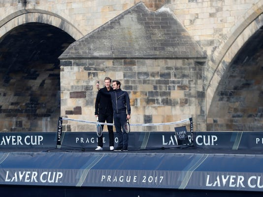 Switzerland's tennis player Roger Federer, right, and Czech Republic's Tomas Berdych, left, pose for a photo during a exhibition match on Vltava river in Prague, Czech Republic, Monday, Feb. 20, 2017. Federer arrived in Prague to promote the Laver Cup, a tournament that will be held in Prague on Sept. 22-24, 2017, pitting six top European players against their counterparts from the rest of the world. The Charles Bridge is in the background. (AP Photo/Petr David Josek)