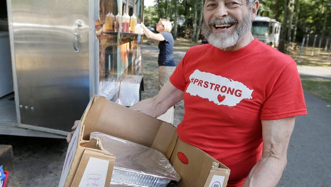 Joseph Badame of Medford helps during a food truck fundraiser for the people of Puerto Rico in the aftermath of Hurricane Maria at Anthony Barber and Victoria Martinez-Barber's home in Medford.