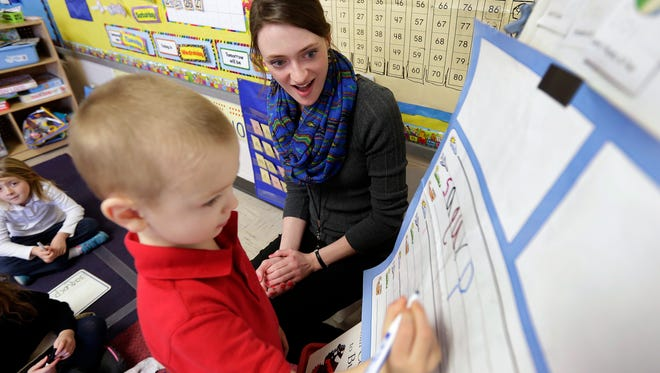 Resurrection Catholic School kindergarten teacher Maggie Hogan works with student Emmett Jensen on writing his letters as she teaches her class Jan. 27, 2016.