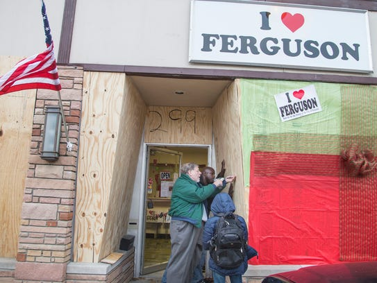 Paul Morris (center front) boards up his store in Ferguson