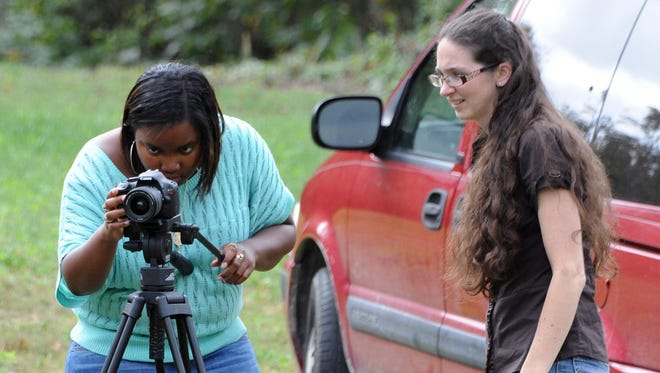 Tori Crenshaw, left, and Shelley Sams set up equipment to work on scenes Friday at a home on Ault Road.