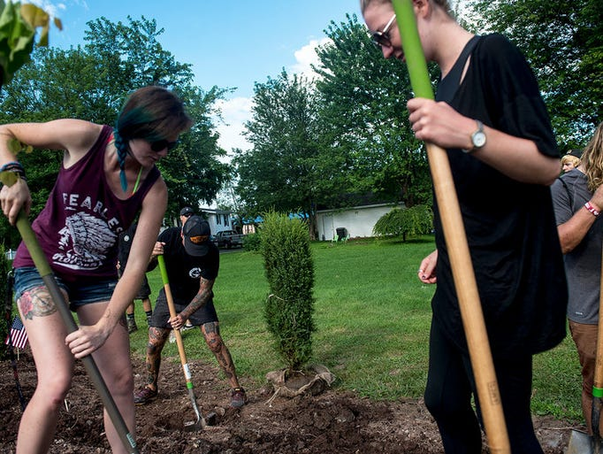 Karla Bossenbery, left, of Detroit, Mich., plants trees